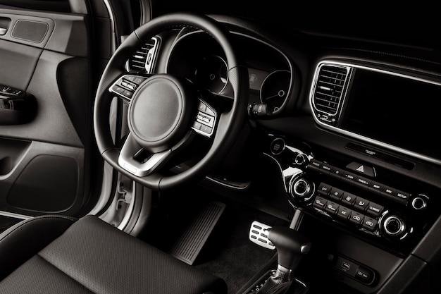 Volante de coche nuevo, detalles lujosos en cuero negro.