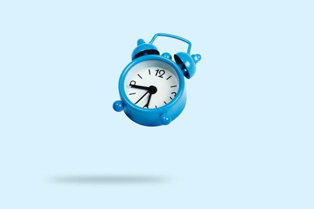 Volar el despertador azul sobre un fondo azul. levitación
