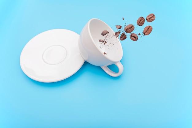 Volcado o volcado taza de café con leche, taza con tazón y granos de café.
