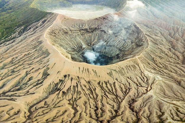 Volcán cráter expulsando humo