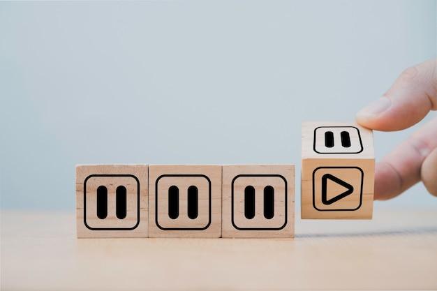 Voltear el cubo de madera a mano para cambiar la pausa o detener para jugar o comenzar, concepto de mentalidad de la gente