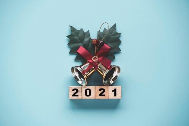 Volteo del bloque de cubos de madera para cambiar el año 2020 al 2021 con campana dorada sobre fondo azul.