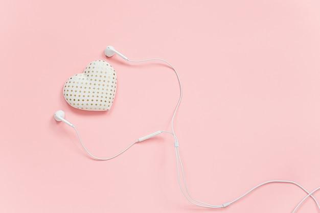 Volumen decorativo textil corazón y auriculares blancos sobre fondo rosa. concepto escucha a tu corazón o amor por la música.