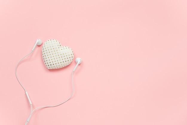Volumen decorativo textil corazón y auriculares blancos sobre fondo rosa. concepto escucha a tu corazón.