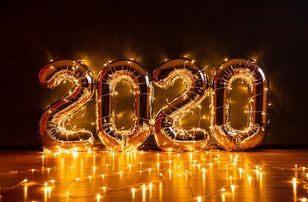 Voluminosas figuras inflables 2020 contra una pared oscura, envueltas en luces navideñas con hermosos reflejos y un lugar para texto