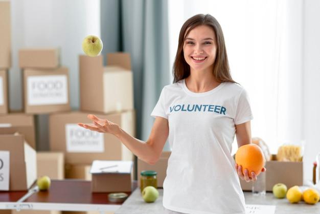 Voluntaria feliz con comida para donación