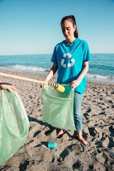 Voluntaria recogiendo basura en la playa
