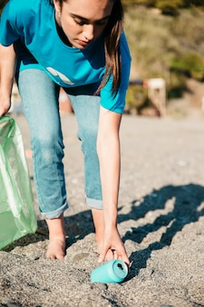 Voluntaria recogiendo lata en la playa