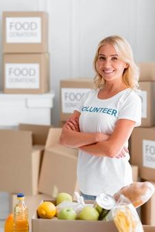 Voluntaria sonriente posando junto a donaciones de alimentos