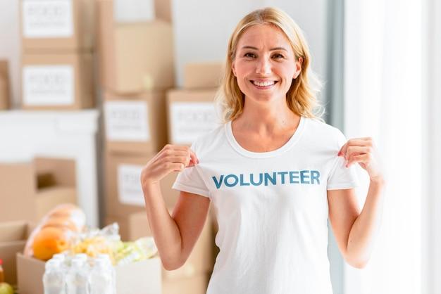 Voluntaria sonriente posando mientras muestra la camiseta
