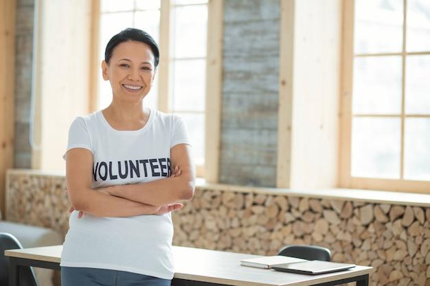 Voluntariado comunitario. voluntaria alegre y vigorosa de pie sobre un fondo borroso y cruzando las manos mientras sonríe