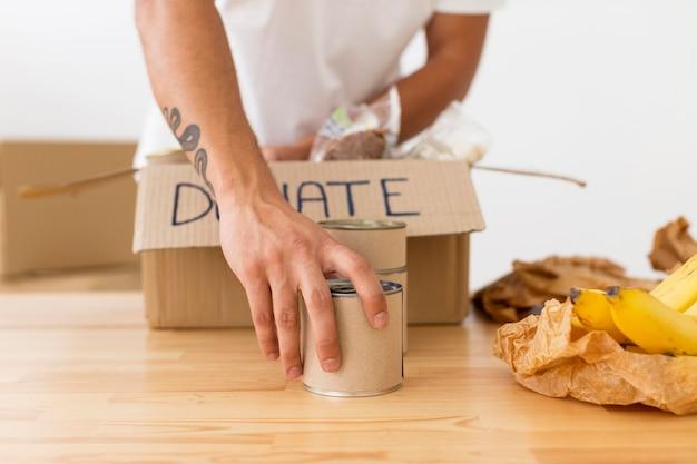 Voluntario colocando latas con comida en primer plano de cajas