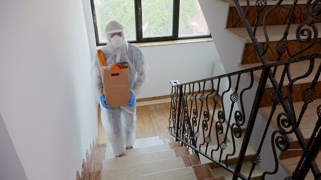 Voluntario entregando comestibles vistiendo un traje de materiales peligrosos contra el covid-19.