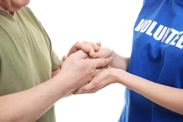 Voluntario femenino joven y hombre mayor tomados de la mano aislados