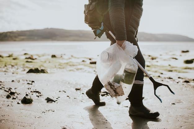 Voluntario de limpieza de playa que lleva una bolsa de basura para la campaña medioambiental