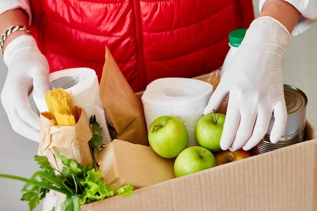 Voluntario en la máscara médica protectora y guantes poniendo comida en caja de donación. repartidor empleado en chaleco rojo caja de embalaje con comida. servicio de cuarentena de pandemia de coronavirus.