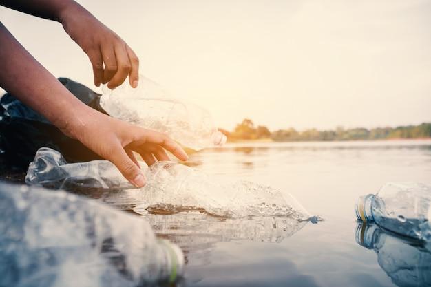El voluntario que recoge una botella de plástico en el río protege el medio ambiente de un concepto de contaminación.