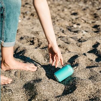 Voluntario recogiendo lata en la playa