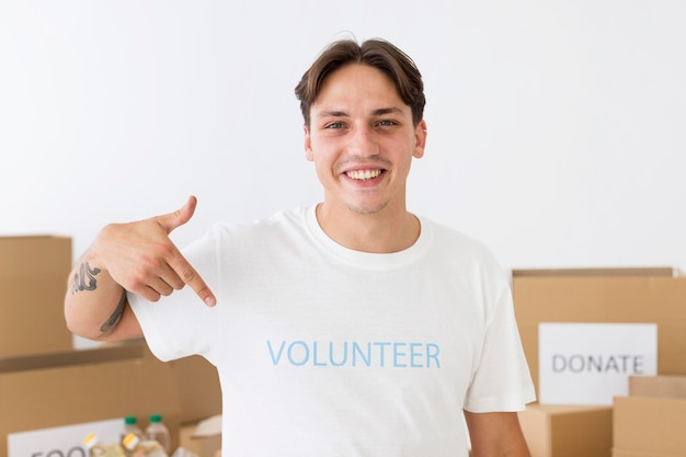 Voluntario sonriente apuntando a su camiseta