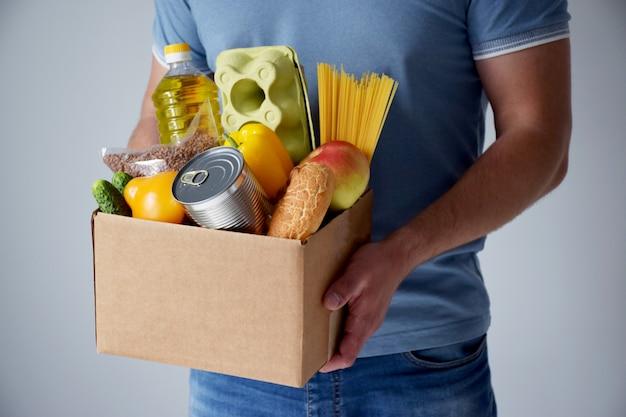 Voluntario sostiene una caja de cartón con donación de alimentos en las manos en la mesa