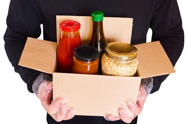 Un voluntario con un suéter negro y guantes desechables entrega una caja de donación con productos. fondo aislado