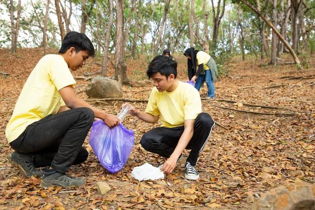 Voluntarios adolescentes con bolsas de plástico.