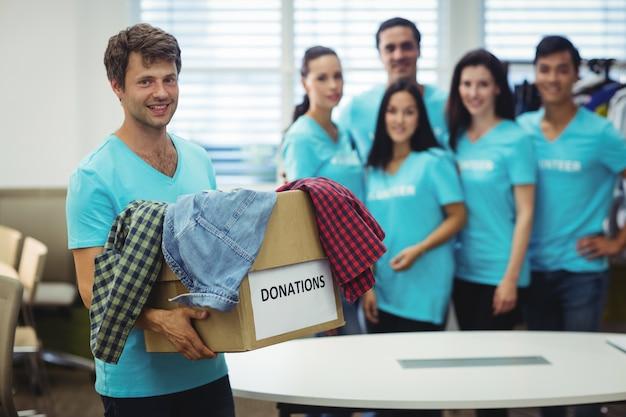 Voluntarios colgar la ropa en caja de donación