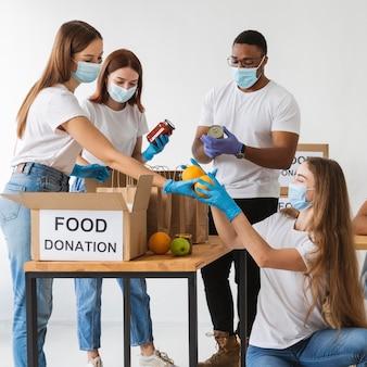 Voluntarios con máscaras médicas preparando cajas de donación.