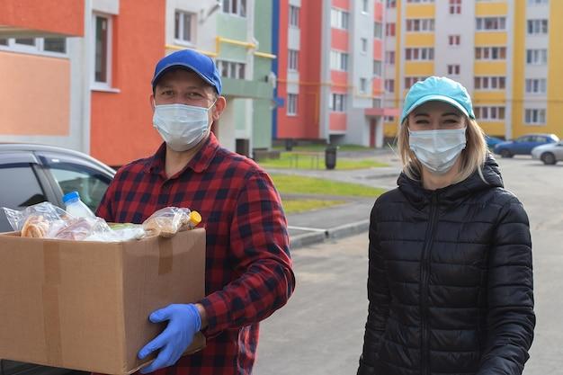Voluntarios con máscaras protectoras con una caja de comida, caminan por la calle