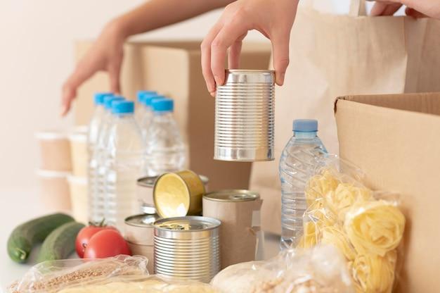 Voluntarios poniendo comida enlatada para donación en caja