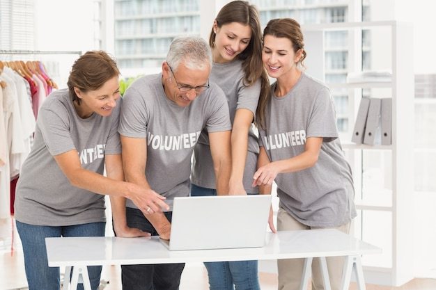 Voluntarios sonrientes apuntando en la computadora portátil