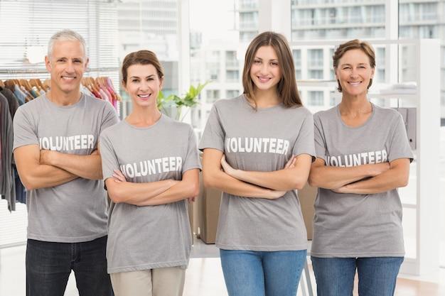 Voluntarios sonrientes con los brazos cruzados