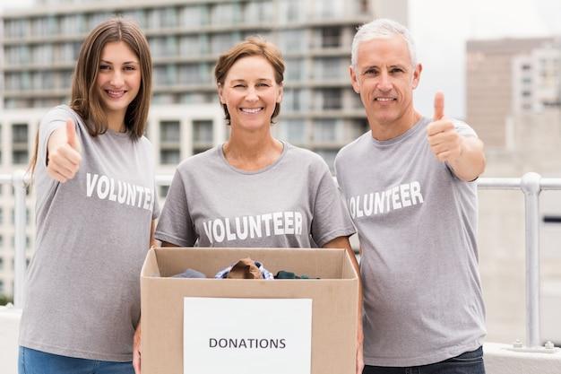 Voluntarios sonrientes con caja de donación haciendo pulgares arriba