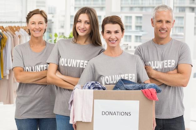 Voluntarios sonrientes con caja de donación