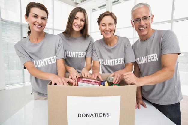 Voluntarios sonrientes clasificando la caja de donaciones