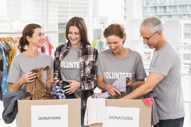 Voluntarios sonrientes clasificando cajas de donación