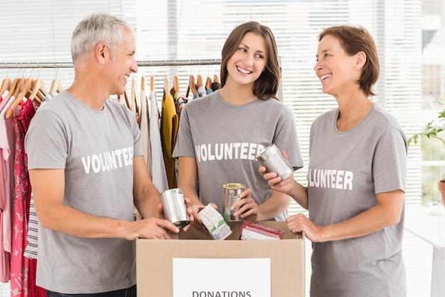 Voluntarios sonrientes clasificando donaciones