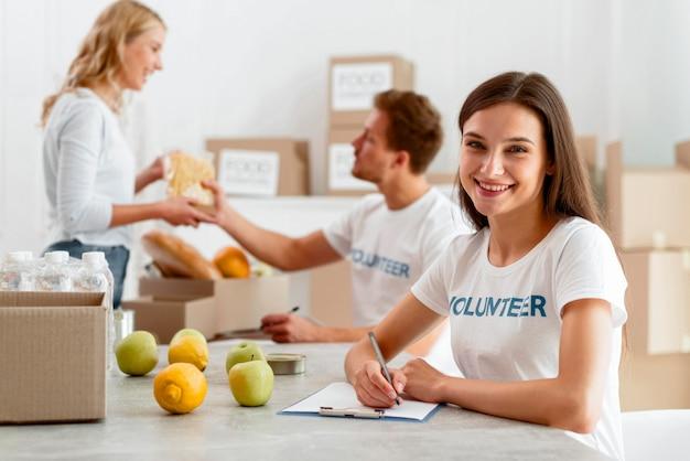 Voluntarios sonrientes que trabajan para donar alimentos