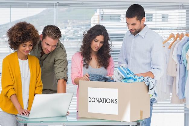 Voluntarios usando una computadora portátil y tomando ropa de una caja de caridad.