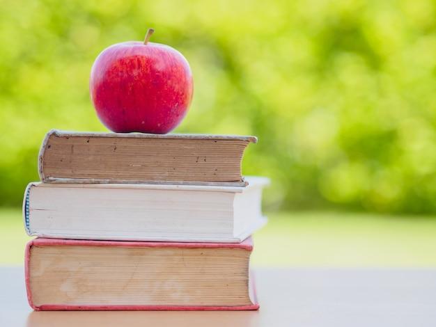 Volver al concepto de escuela. manzana roja poner en la pila de libros antiguos.