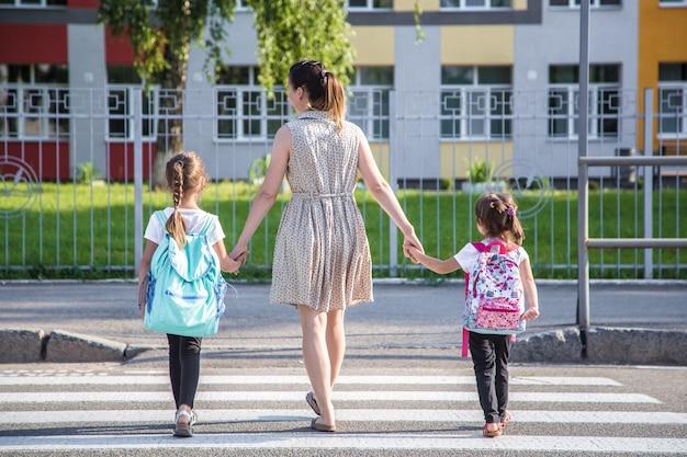 Volver al concepto de educación escolar con niñas, estudiantes de primaria, llevando mochilas para ir a clase tomados de la mano juntos caminando