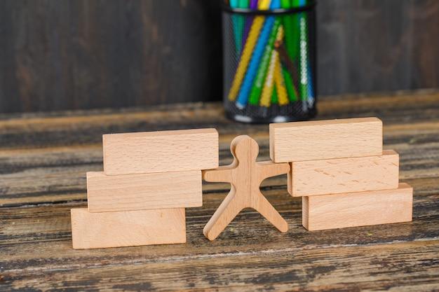 Volver al concepto de escuela con bloques de madera, figura humana, lápices en la mesa de madera vista de ángulo alto.