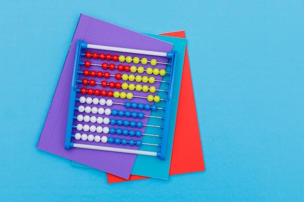 Volver al concepto de escuela con cuadernos, ábaco sobre fondo azul plano lay.