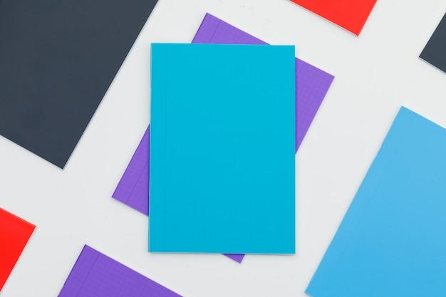 Volver al concepto de escuela con cuadernos multicolores en la pared blanca plana lay.