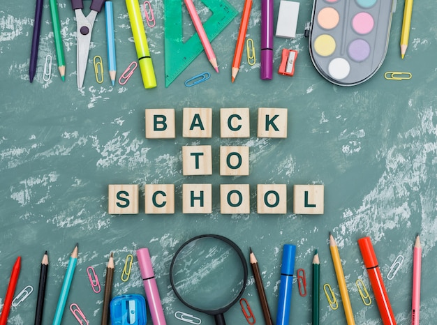 Volver al concepto de escuela con cubos de madera, lupa, útiles escolares en fondo plano de yeso.