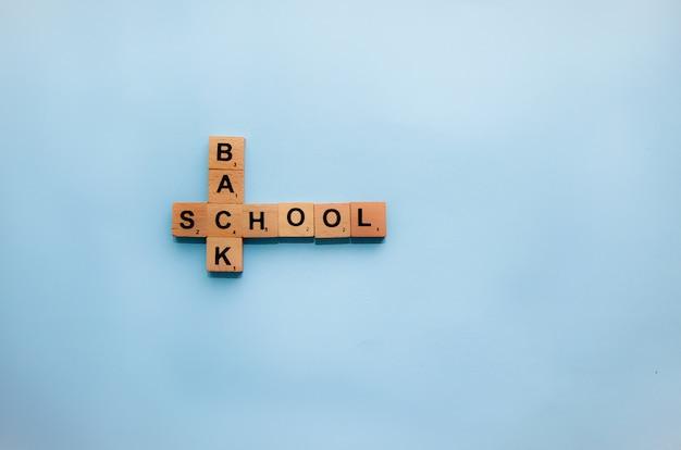 Volver al concepto de escuela. letras de scrabble sobre la mesa.