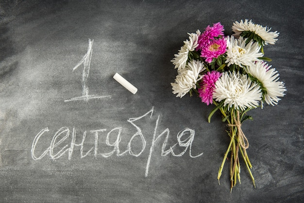 Volver al concepto de escuela. libro y flores astra en tablero negro. 1 de septiembre día.