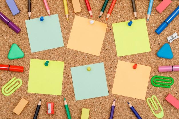 Volver al concepto de escuela con notas adhesivas fijadas, útiles escolares a bordo de fondo plano.