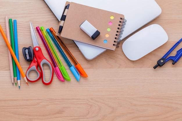 Volver al concepto de escuela con útiles escolares en la mesa de madera.