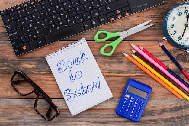 Volver a artículos escolares. accesorios escolares en un escritorio de madera. montón de lápices con tijeras y calculadora. vista superior plana laical.